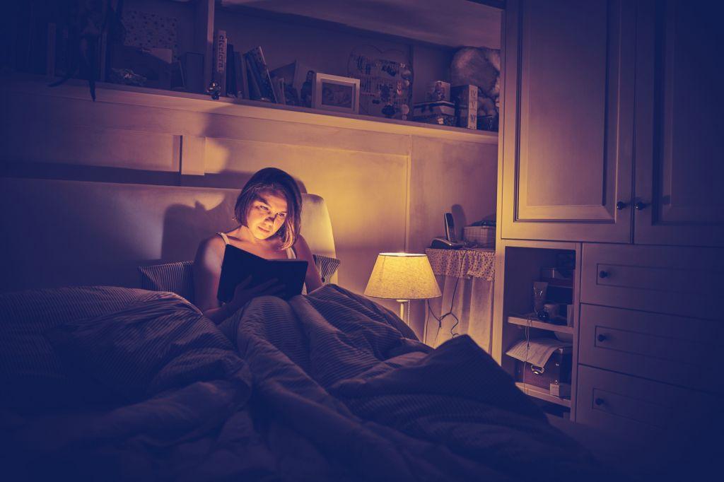 giovane ragazza legge libro a letto